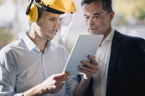 Businessman and man wearing safety helmet looking at tablet - KNSF07733