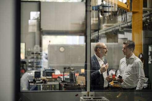 Two businessmen talking in a factory - KNSF07751
