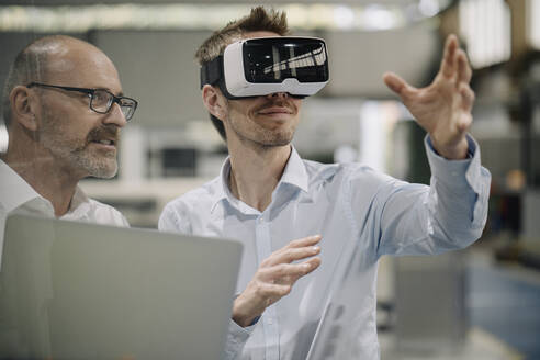 Two men with VR glasses in factory - KNSF07760