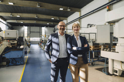 Portrait of confident businessman and businesswoman in a factory - KNSF07775