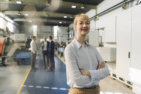 Portrait of a confident businesswoman in a factory with colleagues in backgound - KNSF07781