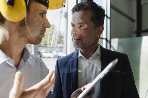 Businessman and man wearing safety helmet facing each other - KNSF07811