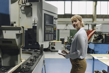 Portrait of a confident businesswoman using wireless keyboard in a factory - KNSF07814