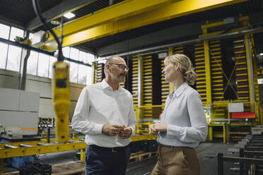 Man and woman talking in a factory - KNSF07817