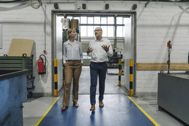 Man and woman walking and talking in a factory - KNSF07823