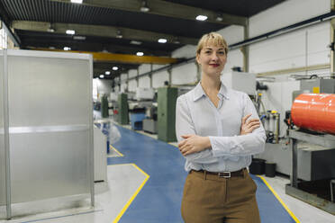 Portrait of a confident businesswoman in a factory - KNSF07826