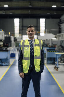 Portrait of a confident businessman wearing a reflective vest in a factory - KNSF07835
