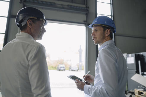 Two men wearing hard hats talking in a factory - KNSF07844