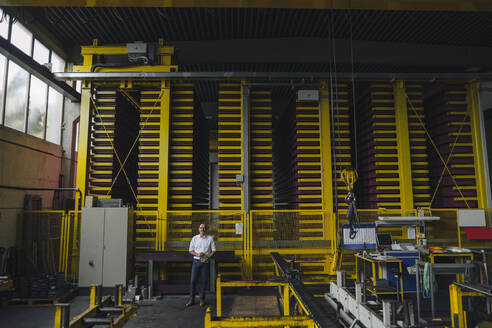 Businessman standing in a factory - KNSF07856