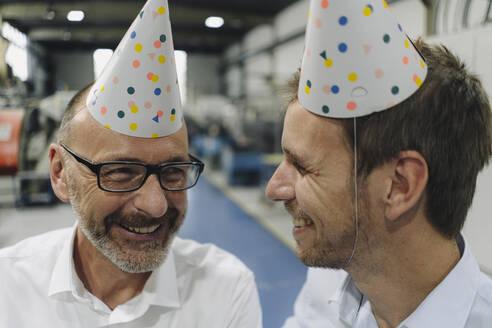 Portrait of two happy businessmen wearing party hats in a factory - KNSF07862
