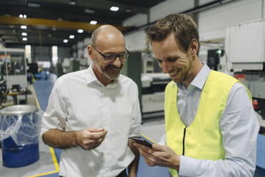 Businessman and man in reflective vest using smartphone in a factory - KNSF07865