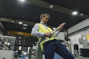 Man wearing reflective vest in a factory playing air guitar on large wrench - KNSF07868
