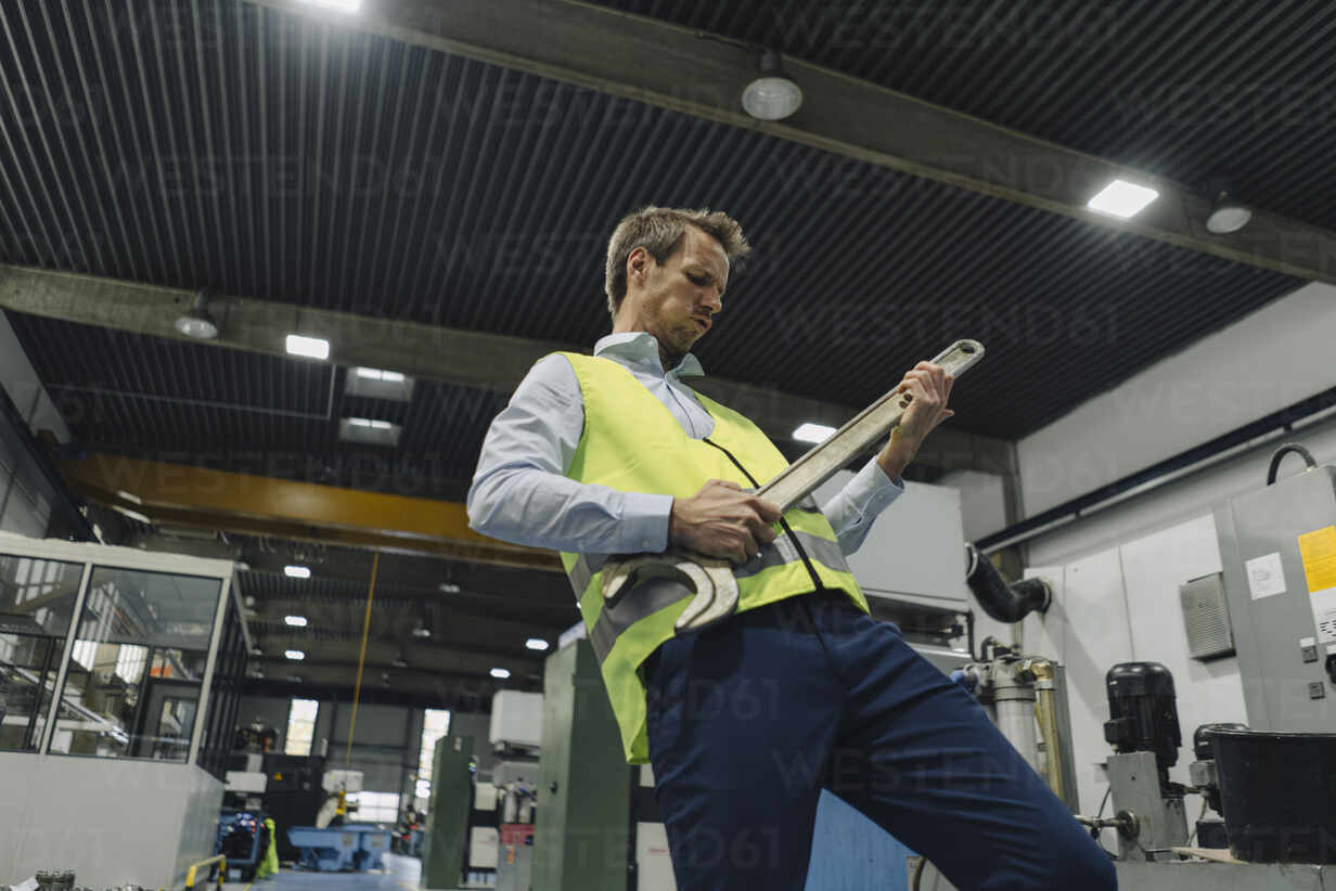 Man wearing reflective vest in a factory playing air guitar on large wrench - KNSF07868 - Kniel Synnatzschke/Westend61