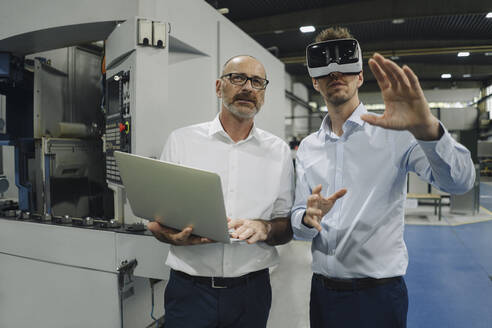 Two men with VR glasses in factory - KNSF07871