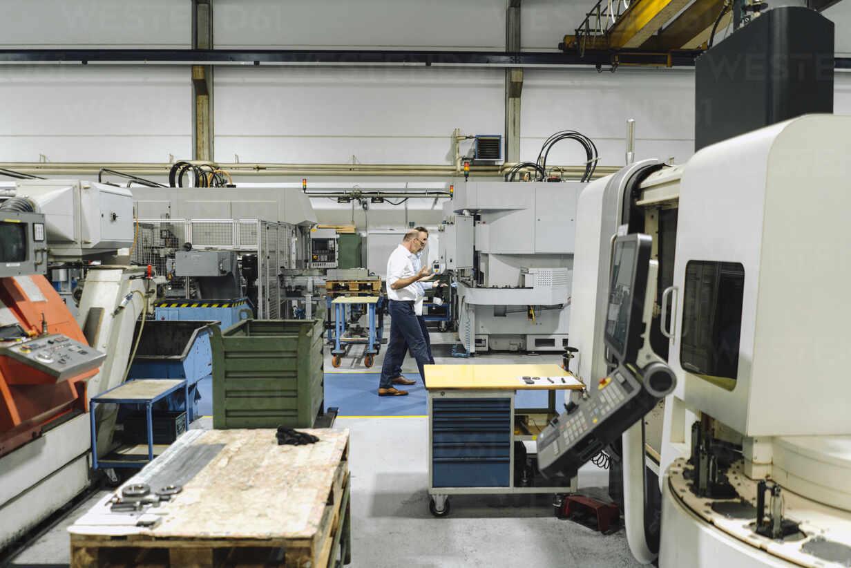 Two men walking and talking in a factory - KNSF07877 - Kniel Synnatzschke/Westend61