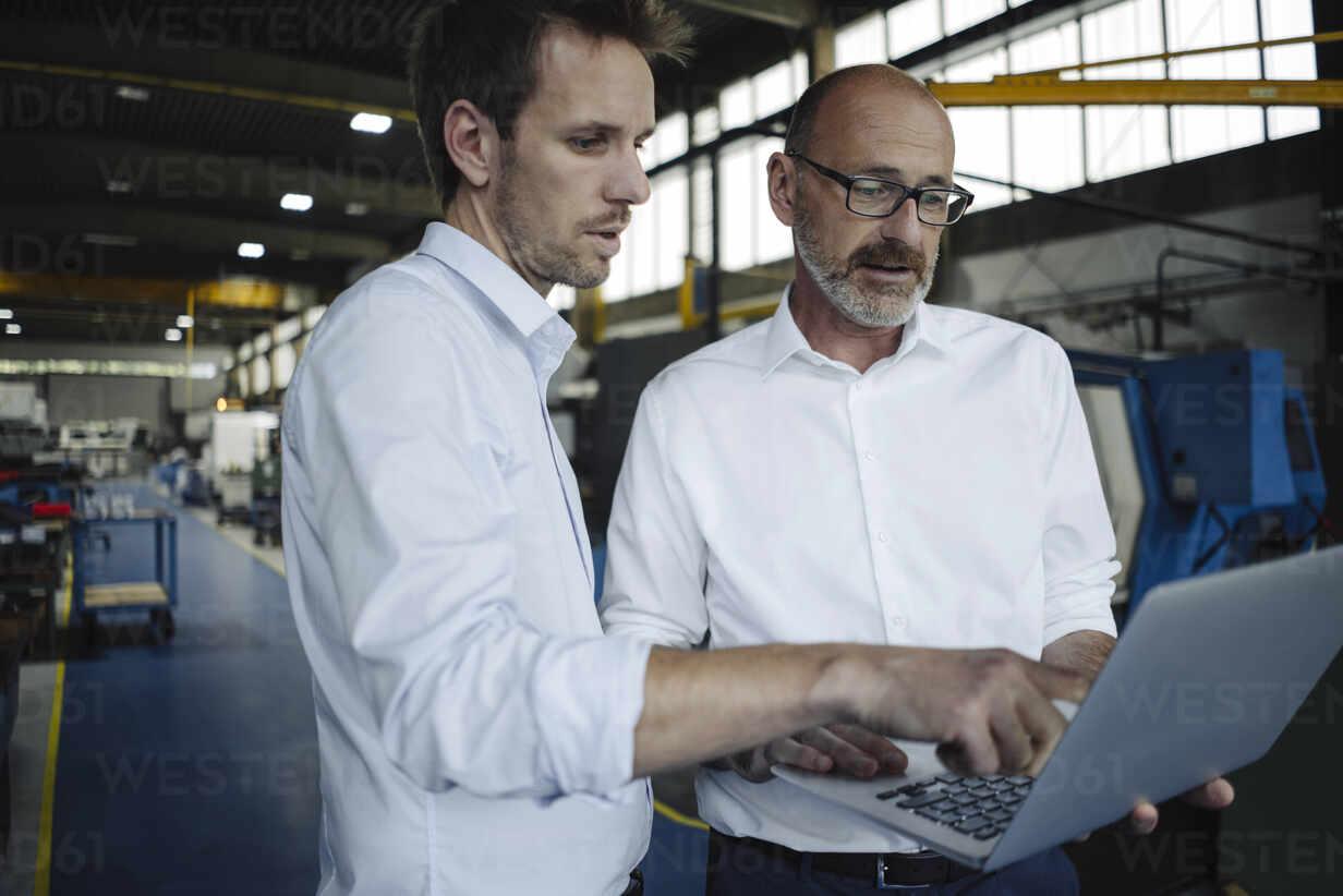 Two men using laptop in a factory - KNSF07880 - Kniel Synnatzschke/Westend61