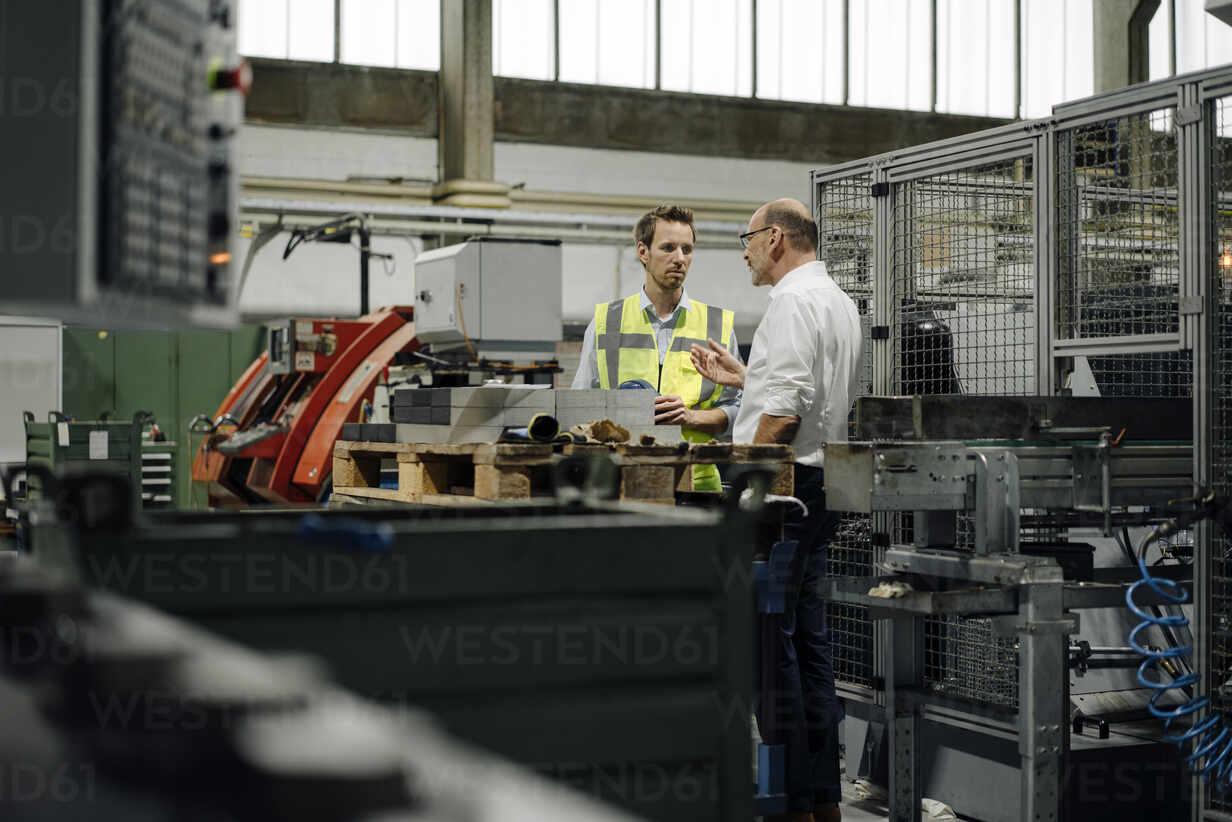 Businessman and man in reflective vest talking in a factory - KNSF07886 - Kniel Synnatzschke/Westend61