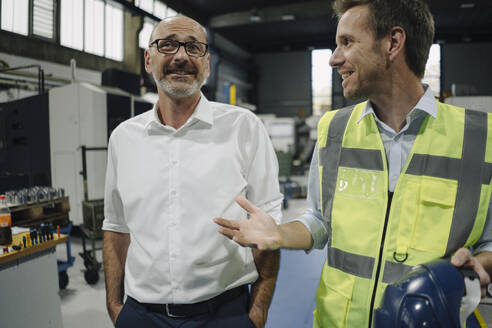 Businessman and man in reflective vest talking in a factory - KNSF07889