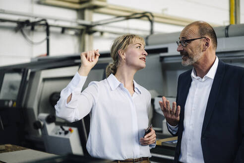 Businessman and woman talking in a factory - KNSF07892