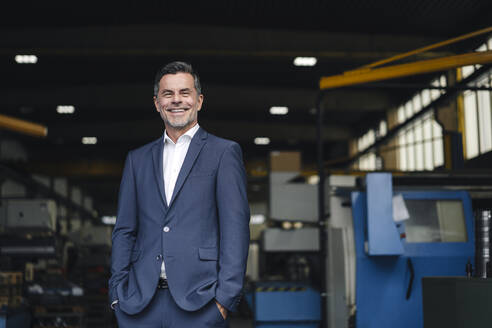 Portrait of a smiling businessman in a factory - KNSF07907