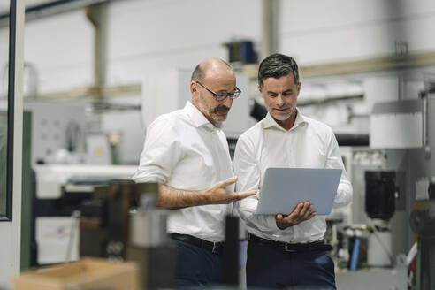 Two businessmen using laptop in a factory - KNSF07919