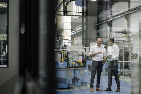 Two businessmen talking in a factory - KNSF07922
