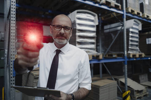 Portrait of man with glowing scanner in factory warehouse - KNSF07928