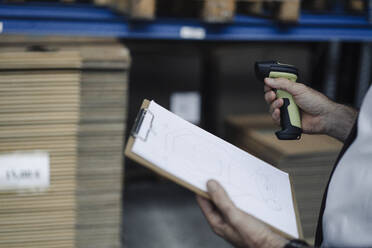 Close-up of man with clipboard and scanner in factory warehouse - KNSF07931