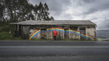 Spain, Province of A Coruna, San Saturnino, Man looking at rainbow painted on abandoned roadside house - RAEF02362