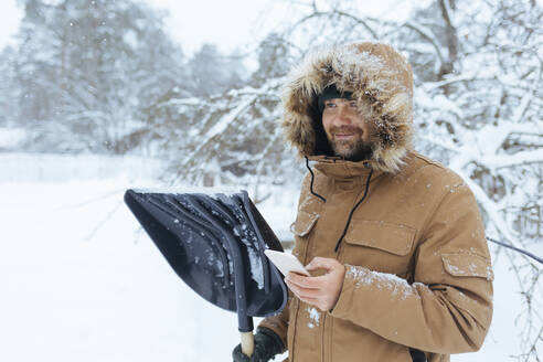 Portrait of smiling man with snow shovel and cell phone - KNTF04422