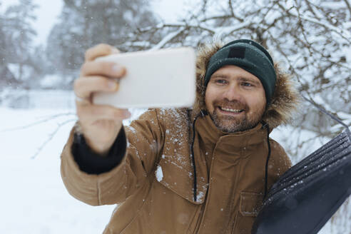 Portrait of smiling man with snow shovel taking selfie with cell phone - KNTF04428