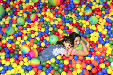 Happy woman lying with her little daughter among many colourful balls - GEMF03472