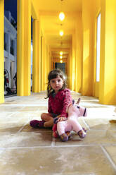 Portrait of little girl sitting on floor with toy unicorn - GEMF03475