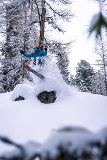 Skier jumping over tree stump in forest whilst in a blizzard - CAVF76204