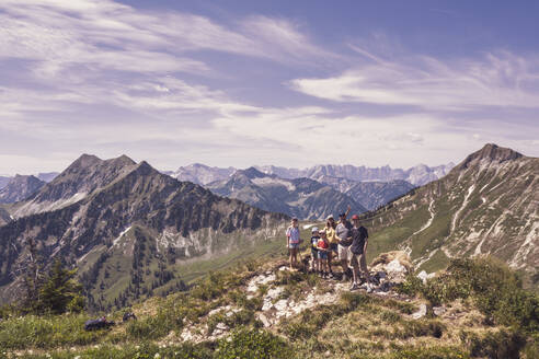 Hiking family standing on mountain peak, Achenkirch, Austria - DHEF00131
