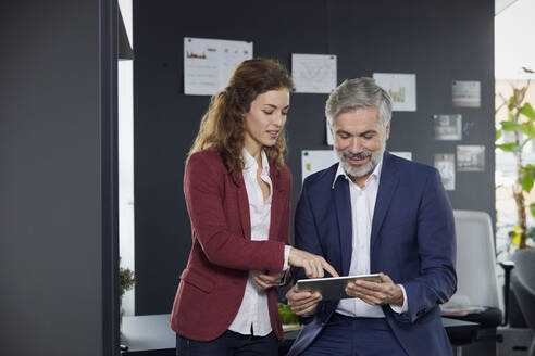 Businessman and businesswoman working together on tablet in office - RBF07069