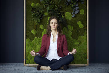 Businesswoman sitting on the floor in green office practicing yoga - RBF07084
