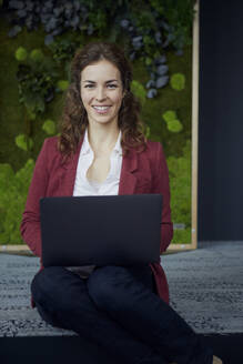 Portrait of smiling businesswoman sitting on the floor in green office using laptop - RBF07087