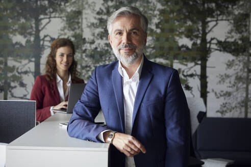 Porrait of smiling businessman in office with businesswoman in background - RBF07096