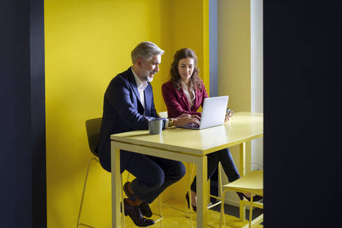 Businessman and businesswoman working together on laptop in office cubicle - RBF07102