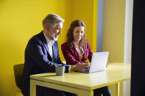 Businessman and businesswoman working together on laptop in office cubicle - RBF07105