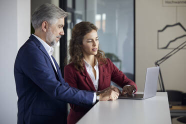 Businessman and businesswoman working together on laptop in office - RBF07108