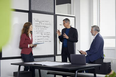 Two businessmen and businesswoman working together on a project in office - RBF07117