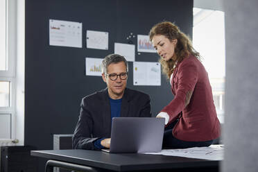 Businessman and businesswoman working together on laptop in office - RBF07129