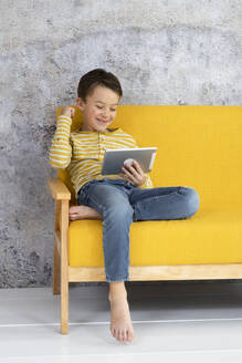 Boy playing with tablet on yellow couch - HMEF00788