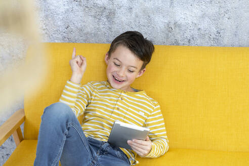 Boy playing with tablet on yellow couch - HMEF00794