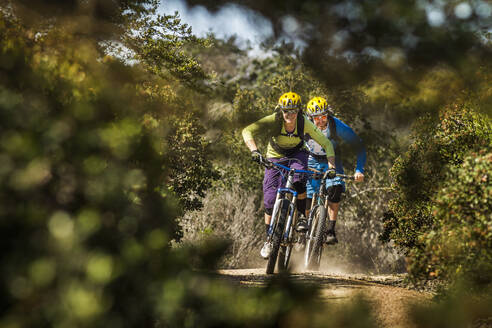 Man and woman on mountainbikes riding on dusty trail, Fort Ord National Monument Park, Monterey, California, USA - MSUF00214
