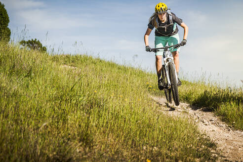 Woman on mountain bike riding down trail in front of blue sky, Santa Cruz, California, USA - MSUF00229