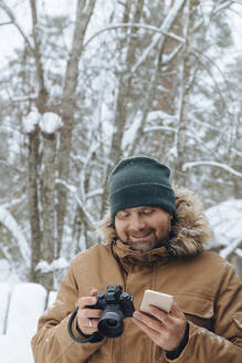 Portrait of relaxed man with digital camera and mobile phone in winter forest - KNTF04489