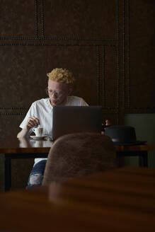 Albino man having a coffee and working on his computer in a cafeteria - VEGF01655